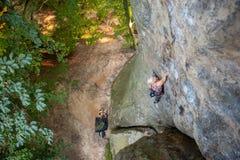 妇女攀岩运动员在岩石墙壁上上升 免版税库存照片