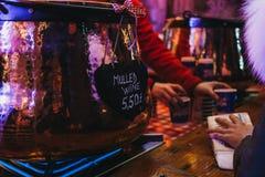 妇女支付被仔细考虑的酒在一个摊位在冬天妙境,伦敦,英国 免版税库存图片