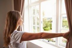 妇女支持的卧室窗口和开幕 免版税库存图片