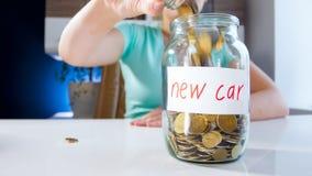 妇女收入和挽救金钱的特写镜头图象买的新的汽车 免版税图库摄影