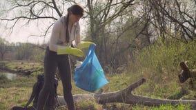 妇女收集垃圾的绿色活动家在森林里 股票视频
