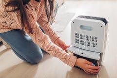 妇女改变的水容器抽湿机在家 在公寓的潮阴阴 现代空气烘干机 免版税库存照片