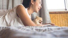 妇女放松与狗在卧室 库存图片