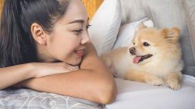 妇女放松与狗在卧室 免版税库存图片