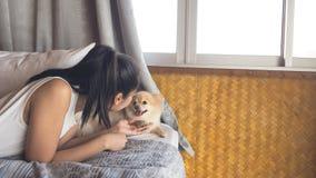 妇女放松与狗在卧室 免版税图库摄影