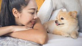妇女放松与狗在卧室 免版税库存照片