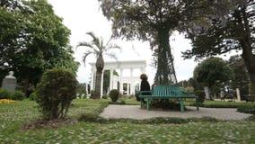 妇女放松在夏天巴统公园的,绿色树和花在城市从事园艺 股票视频