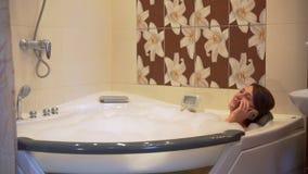 妇女放松在浴缸的泡末浴和谈话在电话 影视素材
