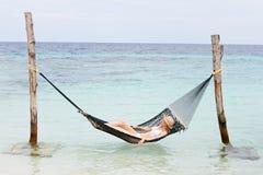 妇女放松在海滩吊床的佩带的比基尼泳装和太阳帽子 库存图片