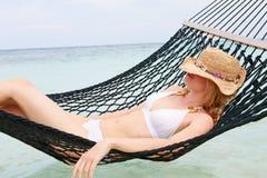 妇女放松在海滩吊床的佩带的比基尼泳装和太阳帽子 图库摄影