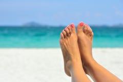 妇女放松在海滩的女孩脚特写镜头 免版税库存图片