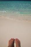 妇女放松在sunbed享用的太阳的海滩的女孩脚特写镜头在晴朗的夏日 含沙海滩的英尺 免版税库存图片