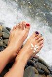 妇女放松在sunbed享用的海滩的女孩脚特写镜头 库存照片