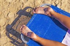 妇女放松在sunbed享用的海滩的女孩脚特写镜头 免版税库存照片
