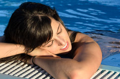 妇女放松晚上入游泳池 免版税图库摄影
