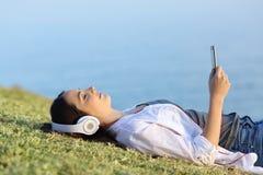 妇女放松的听到在草的音乐 库存图片