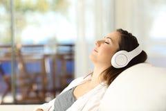 妇女放松的听到在长沙发的音乐 库存图片