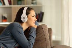 妇女放松的听到音乐和看  免版税库存图片