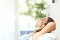妇女放松的在家说谎在长沙发 库存照片