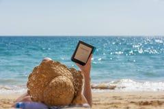 妇女放松,当读在海滩时 免版税库存图片
