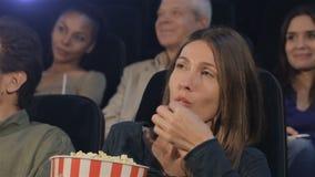 妇女放玉米花入她的嘴在电影院 股票视频