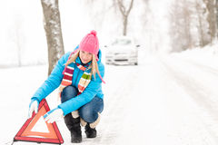 妇女放置警告三角汽车细分冬天 免版税库存照片
