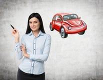 妇女教道路交通规则的依据 一辆红色汽车的剪影在混凝土墙上被画 免版税图库摄影