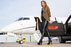 妇女敞篷车汽车和公司私人喷气式飞机 免版税库存图片