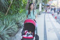 妇女散步与她的在婴儿车里面的婴孩 库存照片