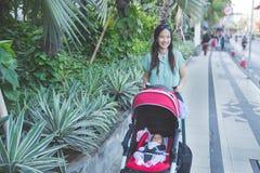 妇女散步与她的在婴儿车里面的婴孩 库存图片
