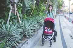 妇女散步与她的在婴儿车里面的婴孩 免版税库存照片