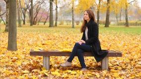 妇女敬佩美好的秋天自然,看在黄色枫叶 股票录像