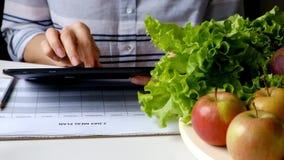 妇女文字使用片剂个人计算机的饮食计划在充分桌上水果和蔬菜 影视素材