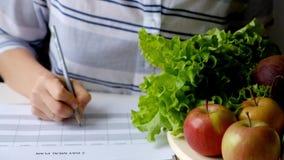 妇女文字在充分桌上的饮食计划水果和蔬菜 股票视频