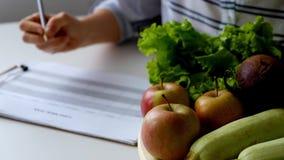 妇女文字在充分桌上的饮食计划水果和蔬菜 股票录像