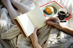 妇女文字笔记本日志在床早餐早晨 免版税图库摄影