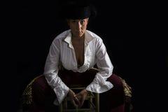 妇女斗牛士坐拿着念珠的一把木椅子 库存照片