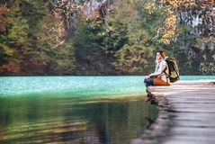 妇女旅客坐在山湖的木桥梁在晴朗的aut 免版税库存照片