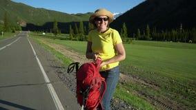 妇女旅客,有一个红色背包的,沿路前进 山区 明亮的太阳,雪山的看法 股票视频
