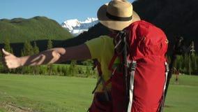 妇女旅客,有一个红色背包的,沿路前进 山区 明亮的太阳,雪山的看法 股票录像
