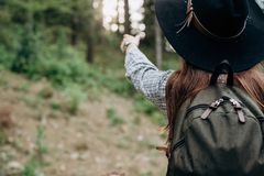 妇女旅客,看和指向她的手美妙的森林 免版税库存照片