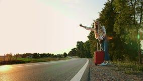 妇女旅客,走在路 疲倦的年轻女人背包徒步旅行者,开始在一条被日光照射了乡下公路的一次旅途 股票录像