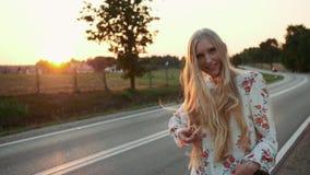 妇女旅客,走在路 疲倦的年轻女人背包徒步旅行者,开始在一条被日光照射了乡下公路的一次旅途 股票视频
