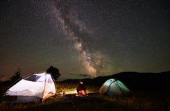 妇女旅游休息在野营在满天星斗的天空和银河下的晚上 库存照片