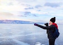 妇女旅游摄影师在冻贝加尔湖表明外部 图库摄影