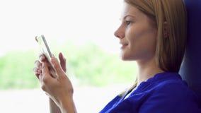 妇女旅游旅行在火车 使用她的智能手机,浏览,读新闻,聊天与朋友 股票录像