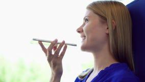 妇女旅游旅行在火车 使用她的智能手机,谈话与朋友 轻微自然震动 股票录像