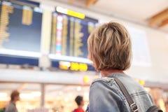妇女旅游看的时间表在机场 免版税库存图片