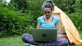 妇女旅游自由职业者在露营地打开膝上型计算机并且工作本质上反对旅游帐篷的背景 影视素材