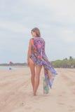 妇女旅游走在一个热带放松旅行假日的暑假海滩佩带的太阳镜和海滩袋子 免版税图库摄影